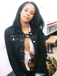 Head and upper torso of a young woman with long, black hair and a broad facial expression, wearing an unbuttoned navy blue jacket and a tank top underneath. Glasses hang from the center of her tank top and she holds a brown purse on the left side of her body.