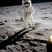 An astronaut in an American Apollo-program spacesuit, standing on the flat, heavily footprinted landing area, with the utterly black sky of space above the horizon.