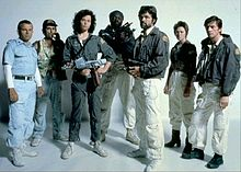 The seven principal cast members of the film stand in front of a white backdrop, in costume and holding prop weapons from the film.