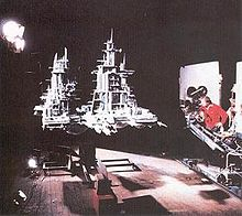 In a film studio, a director operates a crane-mounted camera aimed at a large grey model spacecraft, raised several feet in the air by a support structure underneath. The model is lit from one side by bright studio lights and has tall spires with many pieces protruding from them.