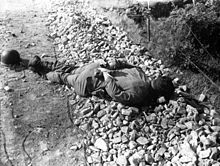 A soldier's body lying on the ground with his hands tied behind his back.