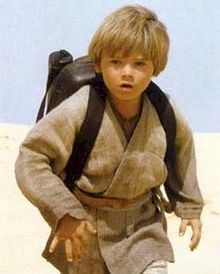 A blonde boy wearing a gray robe and a black backpack walks in a desert.