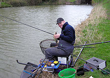 Man seated at the side of the water surrounded by fishing rods and tackle.