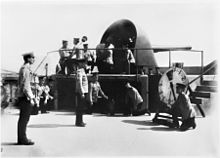 A large gun encassed in an open backed metal turret atop a fort