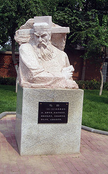 An marble statue depicting the upper half of an elderly man's body. The man has a long beard and thick eyebrows, and is wearing a square cut hat with long, thick, hoizontal protrusions coming out from the sides, near the ears. The carving is angular, and the figure being depicted appears to be in the middle of a sharp turn.