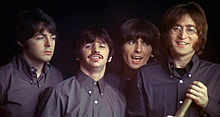 The Beatles, wearing identical dark-grey button-down shirts. They are clean-shaven, except for Starr, who has a moustache. Lennon, wearing mutton chops, holds a folded telescope. All are smiling, except for McCartney, who looks pensive.