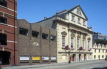 An imposing eighteenth century building with three entrance archways, large first floor windows and an ornate peaked gable end above. On the left a twentieth century grey brick building with a gilded crest and on the right a cream coloured building with four pitched roofs. In front a cobbled street.