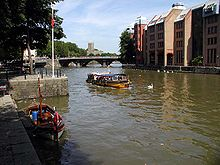 A yellow water taxi on the water between stone quaysides. The far bank has large buildings and in the distance is a three arch bridge.