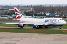 A British Airways Boeing 747-400 in Oneworld livery taxiing on the taxiway, with Heathrow Airport facilities in the background and green grass patch in the foreground