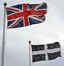 The Union and Cornish flags fluttering in the wind, against a grey, cloudy sky.