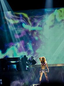 Image of a blond female performer. A big screen is placed behind her. The screen is filled with cosmic and psychodelic images.