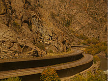 A two tiered highway snaking around bends in a canyon, with some fall foliage visible