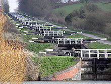 A series of approximately 20 black lock gates with white ends to the paddle arms and wooden railings, each slightly higher than the one below. On the right is a path and on both sides grass and vegetation.