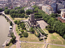 The walls and tower of an old ruined church set in a paved area and surrounded by a park. On the left is water with some pontoons morred and in the background office blocks, streets and church spires.