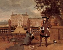 Charles accepts a pineapple from a kneeling man in front of a grand country house