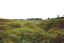 Uneven gullies in a grassy field