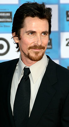 Christian Bale in a black suit at a movie premiere.