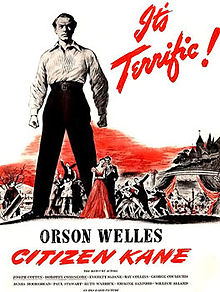 "On a white background, the centre of the poster is dominated by a stern looking man in a white shirt and black trousers towering over a group of people. ""It's terrific!"" appears in red in italics in the top right of the picture tipped 60° to the right. ""Orson Welles"" appears in block letters below the group of people and the man in the white suit. ""Citizen Kane"" appears in red italics below that. The remaining credits are listed in fine print in the bottom of the picture."