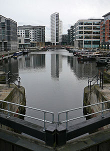 A night-time scene of a dock containing a number of moored canal-boats to left and right and railings around the edges. At the front is part of a lock gate and steps leading down to the water. Around most of the dock are multi-storey modern buildings, some with lighted ground-floors and seats and decorative objects outside. The most prominent of these, at the far end, is a twenty-storey building with curving facades.