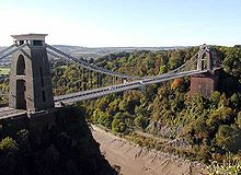 Suspension bridge between two brick built towers, over a wooded gorge, showing mud and water at the bottom. In the distance are hills.