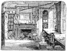 A monochrome illustration of a ramshackle room. Windows allow light to stream in, from the right of the image. Plaster is missing from the ceiling. A large fireplace dominates the far wall, and is surrounded by various cupboards and containers. The floor appears to be formed from planks of wood.