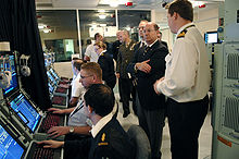 Men sitting at computer terminals with other men and a woman standing behind them