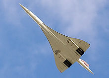 A view from below of an aeroplane in flight, with a slender fuselage and swept back wings.
