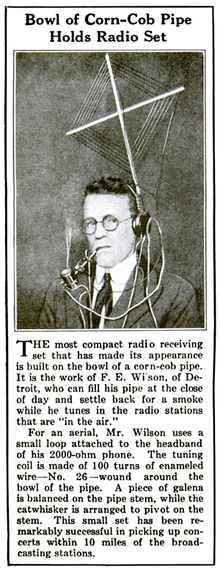 Newspaper clipping with photo showing a man wearing headphones and smoking a pipe; attached to the headphones is a diamond-shaped multiturn aerial, and the pipe bowl is wound with wire; the crystal detector is mounted on the pipe stem. Text in the clipping describes the photo and says this rig could pick up stations up to 10 miles away.
