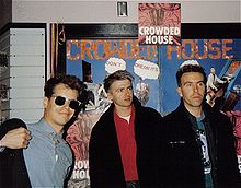 Three men are standing in front of posters advertising the band. Man at left is wearing sunglasses, smiling and adjusting his dark jacket. Man in middle is staring to his left and wears a similar dark jacket. Third man is also staring to his left and has a dark jacket.