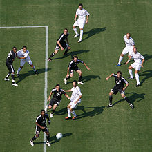 Six soccer players in black and five in white views from above look up for a moving soccer ball coming toward them.