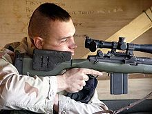 color photo of a Marine peering through the optics of a large rifle