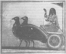 A grey-scale image depicting woman wearing a sari and gold ornaments sitting on a chariot pulled by two large black birds and holding a winnowing basket.