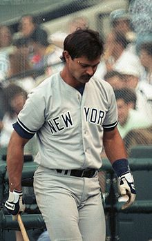 Don Mattingly wearing a gray baseball uniform holds a baseball bat with his left arm.