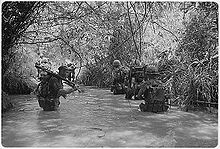black & white photo Marines of Company H, 2nd Battalion, 4th Marine Regiment wading through a waist deep river in a jungle