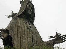 A metal statute of a woman wearing a hooded cloak with a kindly expression whose shoulder and outstretched hand are perched on by stylized birds