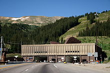 "Automobiles are driving on a road leading to one of two openings in a building against a mountain. Letters above each opening read ""Johnson Tunnel 1979"" and ""Eisenhower Tunnel 1973"". On the roof of the building, large ventilation hoods are visible."