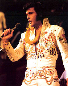 Presley, mutton-chopped and fuller-faced, sings into a handheld microphone. A golden lei is draped around his neck, and he wears a high-collared white jumpsuit resplendent with red, blue, and gold bangles.
