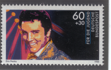 A horizontally formatted stamp with a close-up illustration of a young, smiling Presley. A bank of spotlights shines behind him.