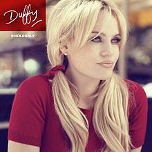 "Image of a blonde woman wearing a red T-shirt with her hair in pigtails and with her arms drawn in to her sides. She is staring off-centre to her left and the background appears to have been blurred. In the left corner, the word ""Duffy"" is written in a red box in signature style. Below is the word ""ENDLESSLY"" in smaller writing."