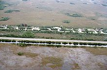 A color photograph taken from the air showing the Everglades bisected by a highway; at the bottom is a sawgrass field flooded with water bordered by a full canal; at the top are some homes and a dry sawgrass field