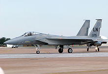 Gray jet aircraft taxiing left before take off, carrying no weapons under wings.