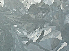 Merged elongated crystals of various shades of gray.