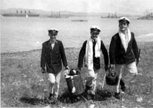 Black-and-white photo of three young men wearing World War I midshipmen uniforms carrying supplies for a picnic on a beach with three ships in the background.