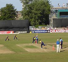 A cricket match with fielders and batmen wearing coloured kit. A bowler delivers a ball to one of the batsman. Some of the crowd can be seen behind advertising hoardings and in front of trees and a scaffold construction.