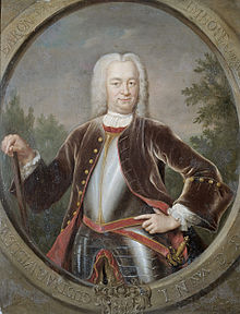 A portrait of Governor General van Imhoff in a large white wig and black suitcoat over plate armour. He is carrying a cane in his left hand and has a sword sheathed on his right side.