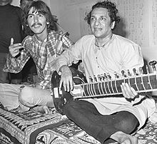 Black-and-white picture of two men, one, in the foreground to the right, in his mid-forties, and the other, in the background to the left, in his mid-twenties. Both are sitting cross-legged on rugs, and the man on the right holds a sitar.