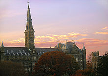 A large Gothic style stone building dominated by a tall clocktower with a pinkish sunset behind it.