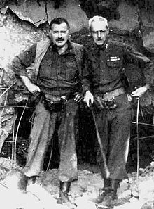 a dark haired man with mustache dressed in army boots, tucked in muddy pants, shirt and vest, with a light haired man dressed in army clothing standing in front of rubble