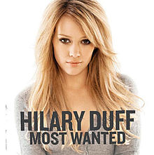 "The portrait of a blonde young woman sitting in front of a white background. She is sitting, looking into the camera. She is wearing a gray colored, full-sleeved top. To the bottom of the picture, the words ""HILARY DUFF"" and ""MOST WANTED"" are printed in black block letters."
