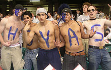 Five young shirtless men pose defiantly in a crowd. Each has a letter in blue on their chests to spell HOYAS.